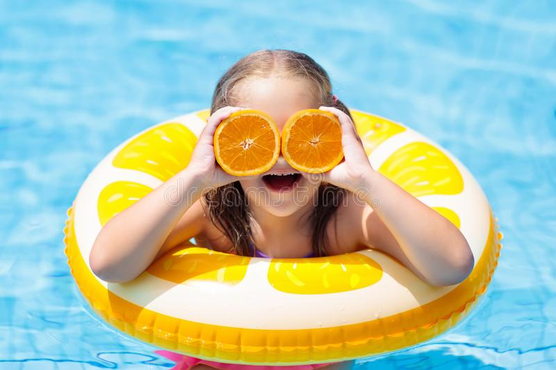 Child in swimming pool. Kid eating orange. stock photography