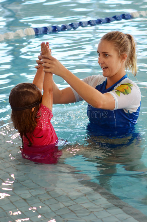 Child swimming pool lesson stock images