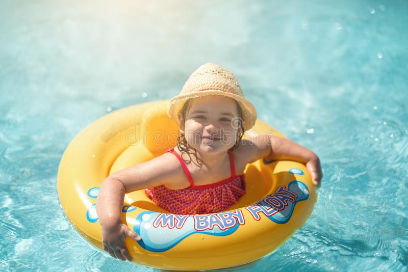 Child In Swimming Pool with ring. Summer Vacation With Kids. stock photos