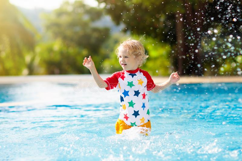 Child in swimming pool. Summer vacation with kids. Child playing in swimming pool. Summer vacation with kids. Little boy jumping into water during exotic holiday stock photo