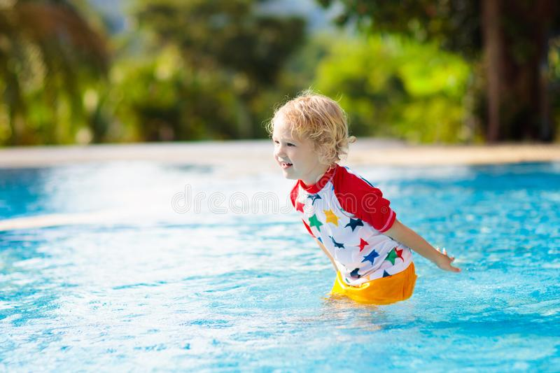 Child in swimming pool. Summer vacation with kids. Child playing in swimming pool. Summer vacation with kids. Little boy jumping into water during exotic holiday royalty free stock photography