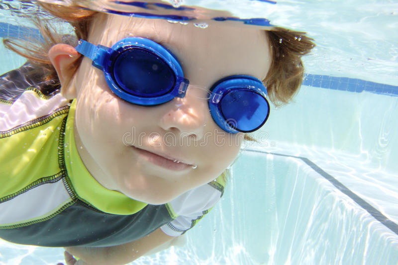 Child Swimming in Pool Underwater. Child, kid, diving and swimming in pool underwater, summer or sports theme royalty free stock photos
