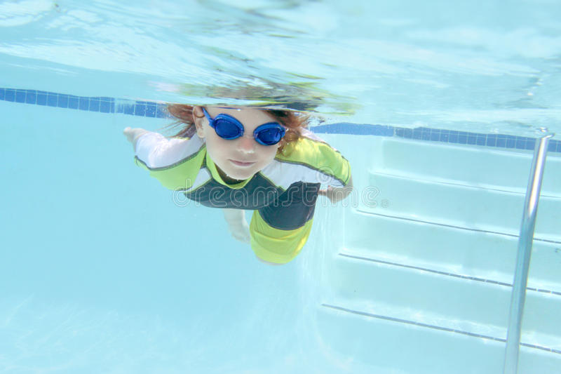 Child Swimming in Pool Underwater. Child, kid, diving and swimming in pool underwater, summer or sports theme stock photography