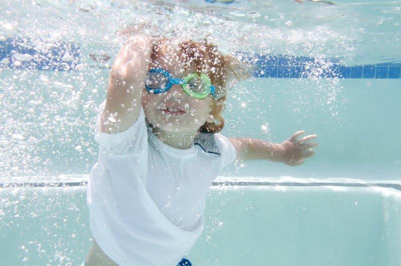 Child Swimming in Pool Underwater. Child, kid, diving and swimming in pool underwater, summer or sports theme stock photos