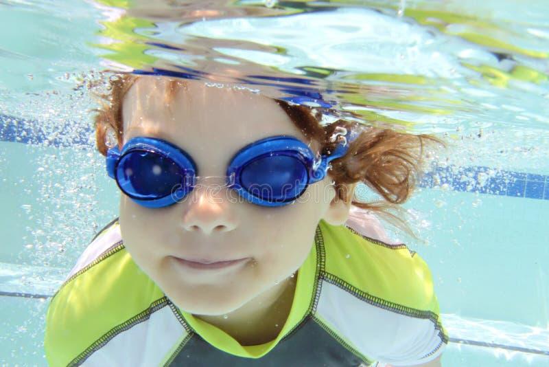 Child Swimming in Pool Underwater. Child, kid, diving and swimming in pool underwater, summer or sports theme stock photo