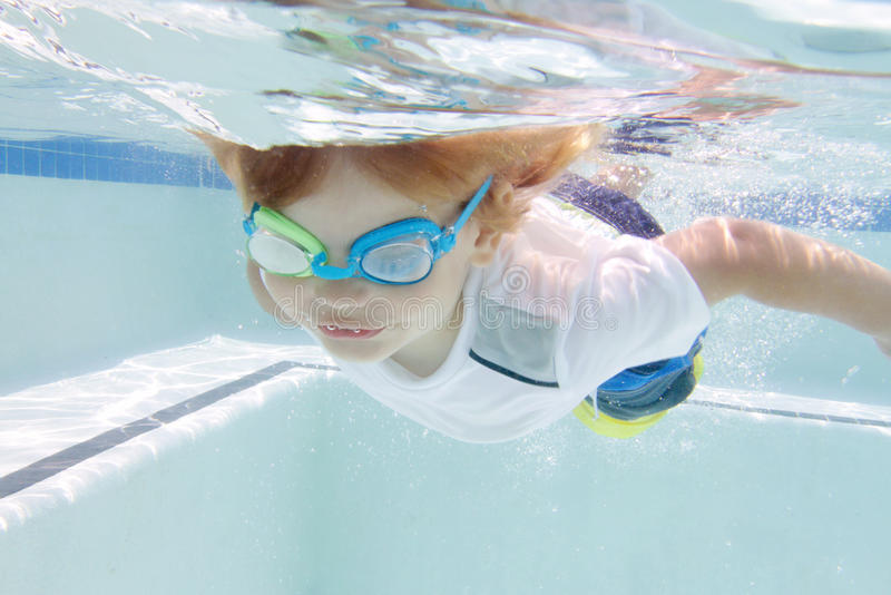 Child Swimming in Pool Underwater. Child, kid, diving and swimming in pool underwater, summer or sports theme stock images