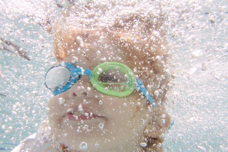 Child Swimming in Pool Underwater. Child, kid, diving and swimming in pool underwater, summer or sports theme royalty free stock photo