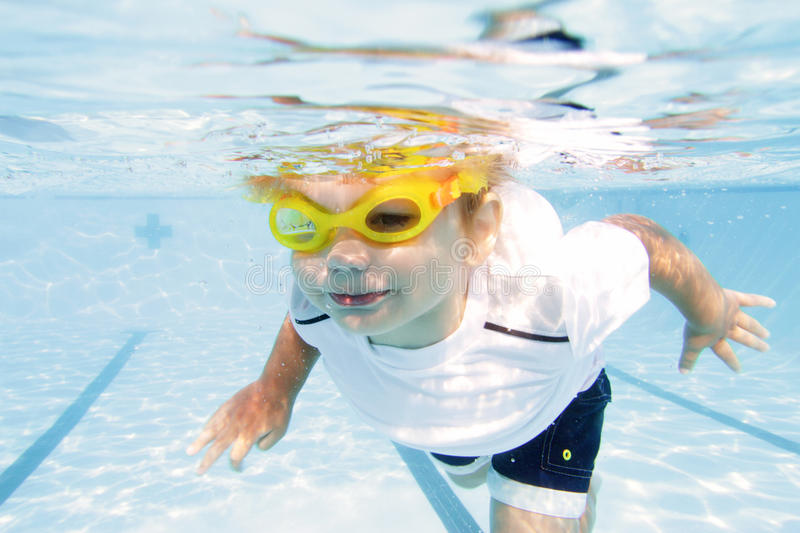 Child Swimming in Pool Underwater. Child, kid, diving and swimming in pool underwater, summer or sports theme royalty free stock images