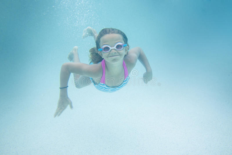 Child swimming underwater in an outdoor pool. A cute smiling little girl swimming underwater in an outdoor swimming pool stock photo