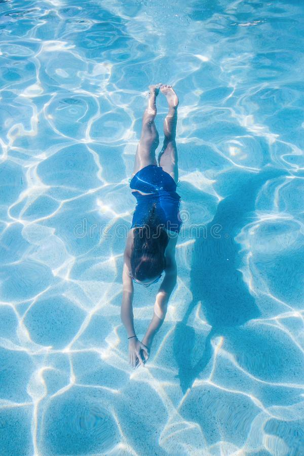Child swimming underwater in an outdoor pool. A little girl swimming underwater in an outdoor swimming pool. View from above. Floating through the crystal blue royalty free stock photos