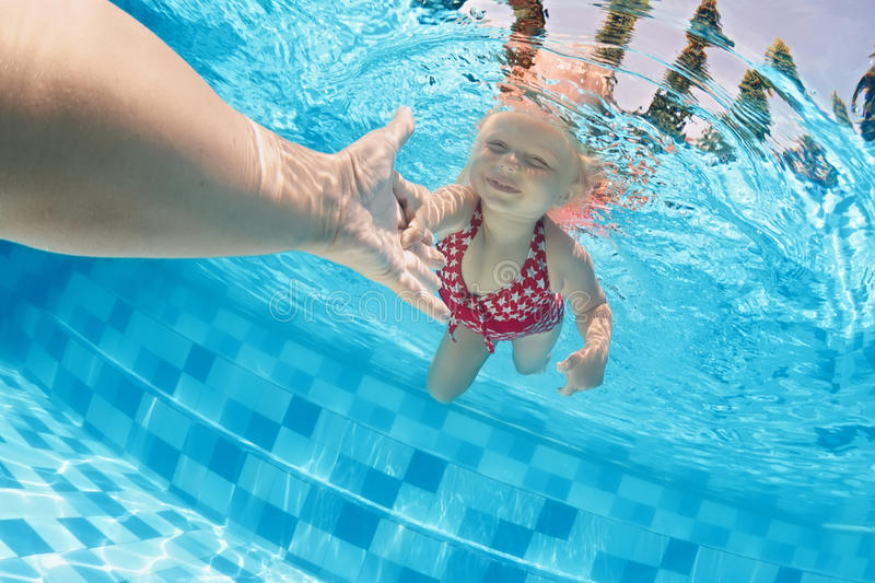 Child swimming underwater in the pool with parents stock photos