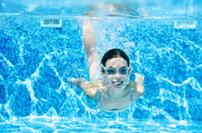Child swims underwater in swimming pool, happy active teenager girl dives and has fun under water, kid fitness and sport stock images
