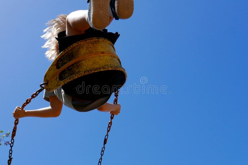 Child swinging high on a playground swing stock photography