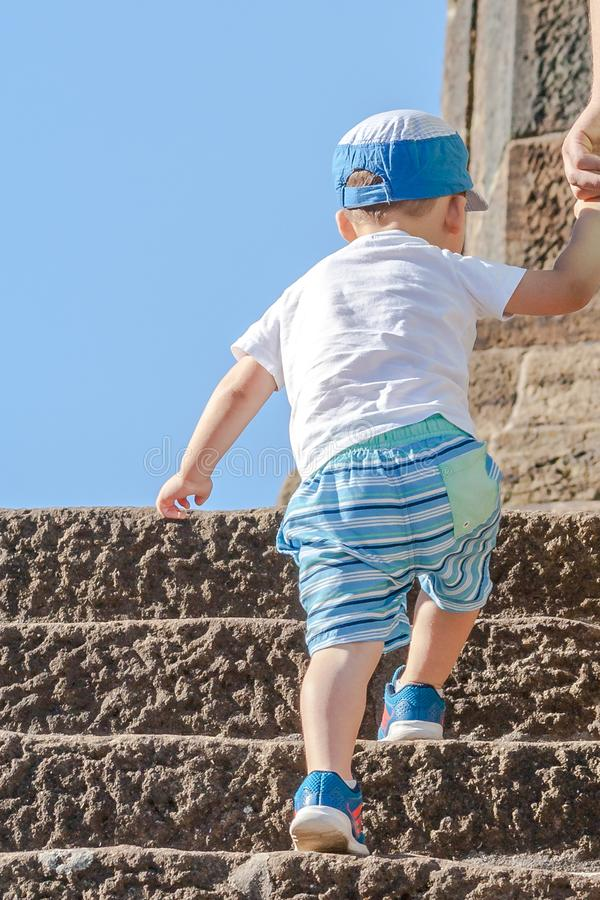 The child in a T-shirt, shorts and a cap goes up the stairs. Picture taken from the back royalty free stock photography