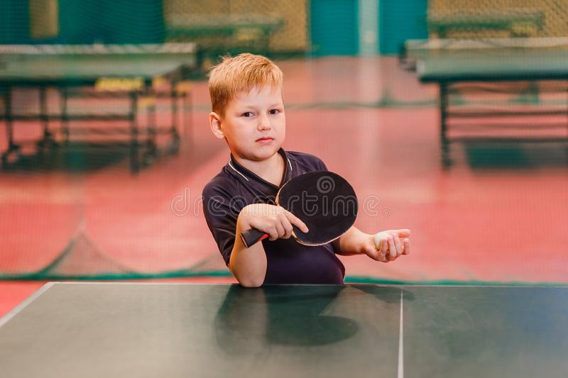Child table tennis player holding a ball and a rocket stock images