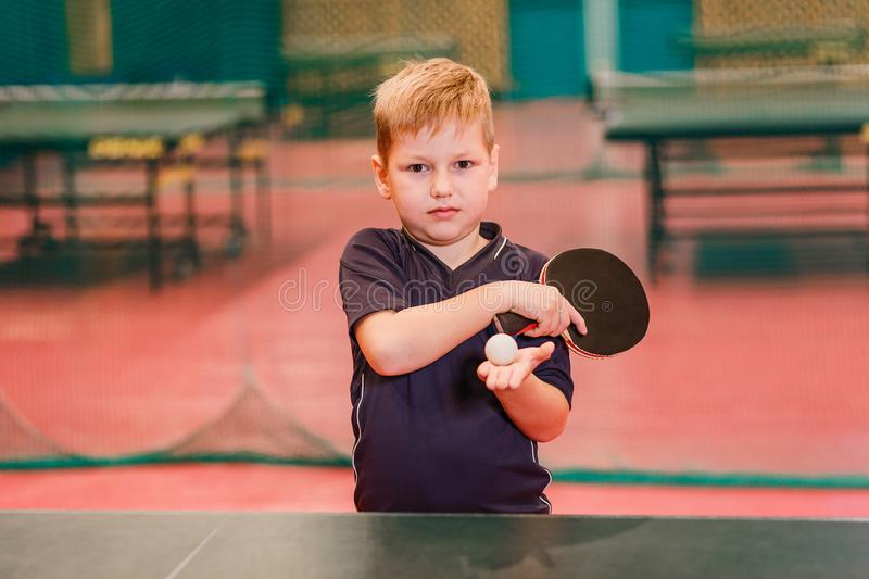 Child table tennis player holding a ball and a rocket in the gym stock photos