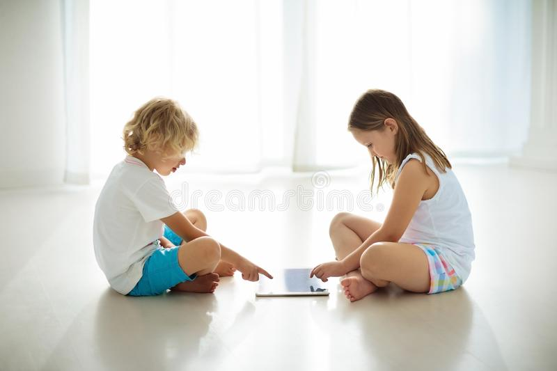 Child with tablet computer. PC for kids. Child with touch screen tablet pc. Kid playing computer game. Little girl and boy in white bedroom reading on digital stock photography