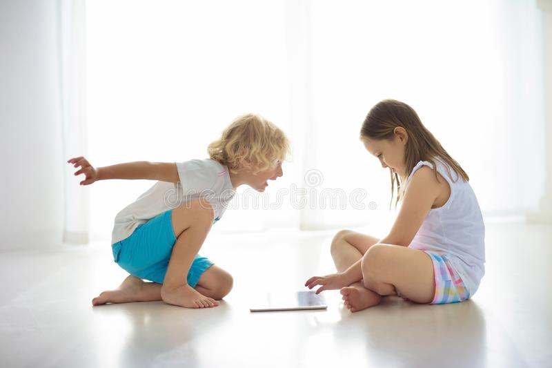 Child with tablet computer. PC for kids. Child with touch screen tablet pc. Kid playing computer game. Little girl and boy in white bedroom reading on digital royalty free stock photos