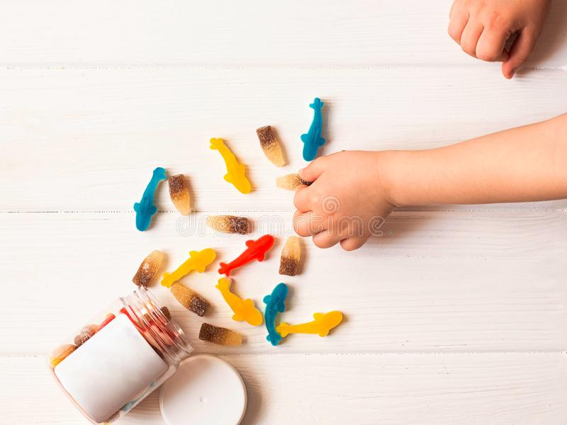 Child takes candy. Multi-colored sweets. Baby hands. White wood background stock photo