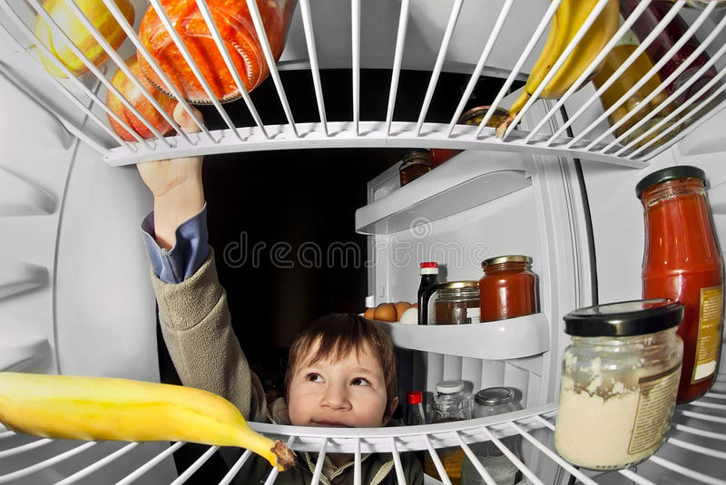 Child takes food from the refrigerator royalty free stock photo
