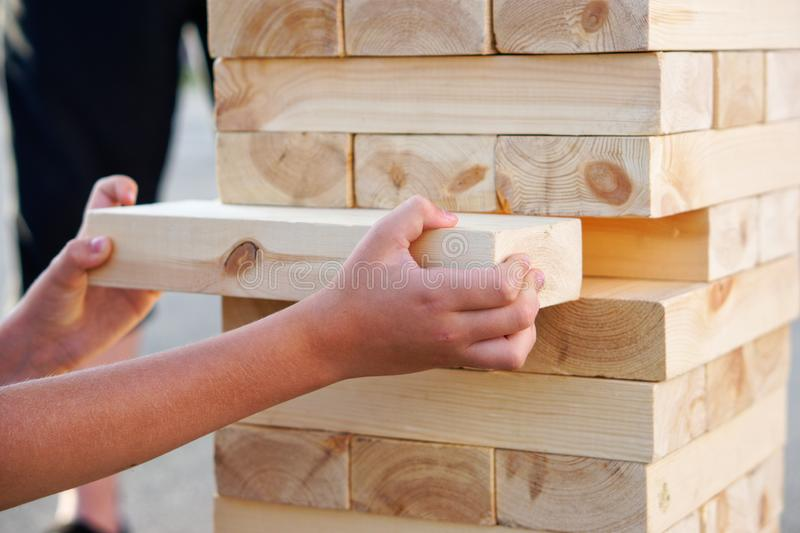 A child takes out one bar from the tower while playing a giant jenga. Outside. Daylight stock photo