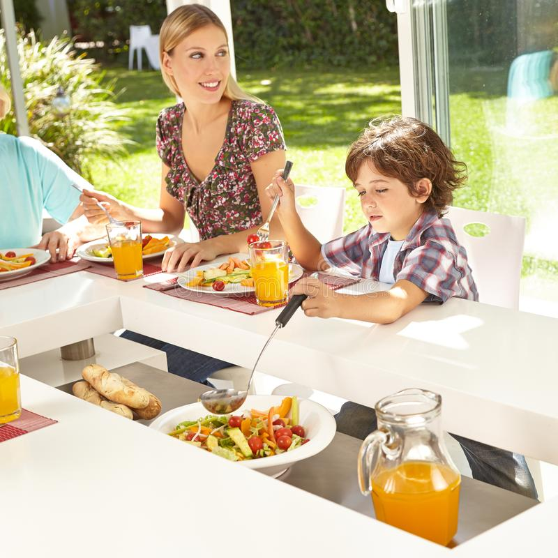 Child takes salad with trowel at the table stock photos