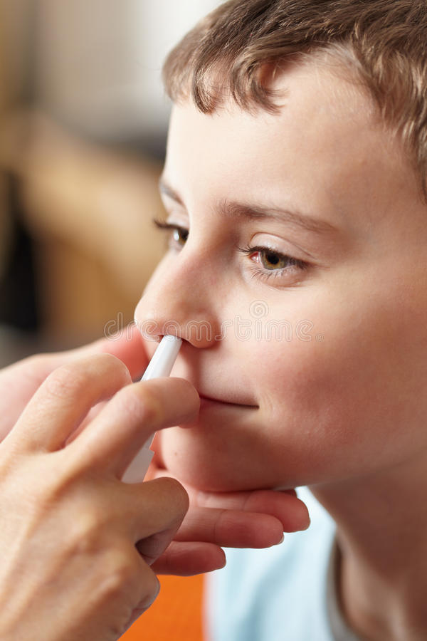 Child taking a dose of nasal spray. Woman doctor hands giving a boy a dose of nasal spray against flu royalty free stock images