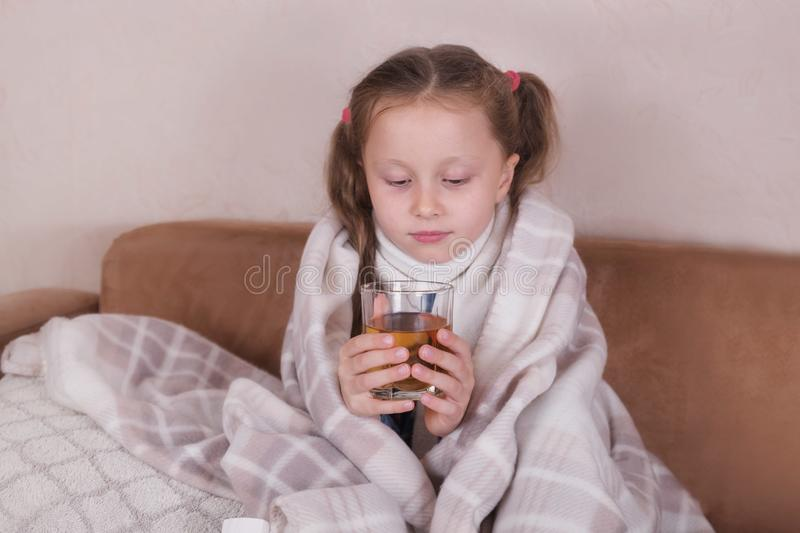 Child taking medicine. Sick girl with scarf lying on bed royalty free stock image