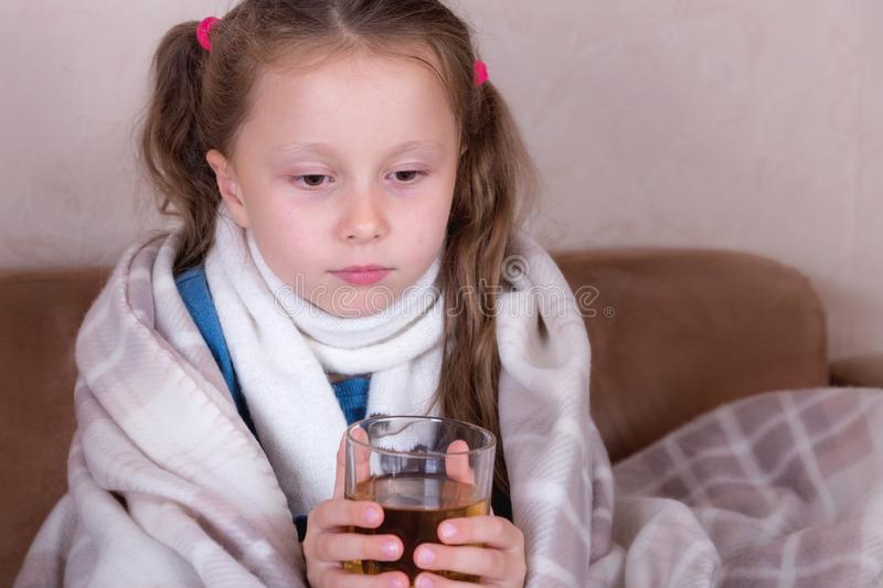 Child taking medicine. Sick girl with scarf lying on bed royalty free stock photo