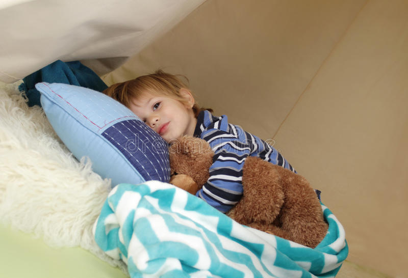 Child Taking a Nap, Resting in a Play Tent Teepee. Child, kid, taking a nap, resting in a play tent teepee stock image