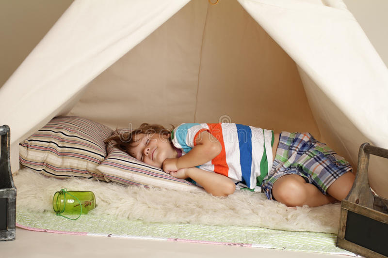 Child taking a nap in a teepee tent royalty free stock photography