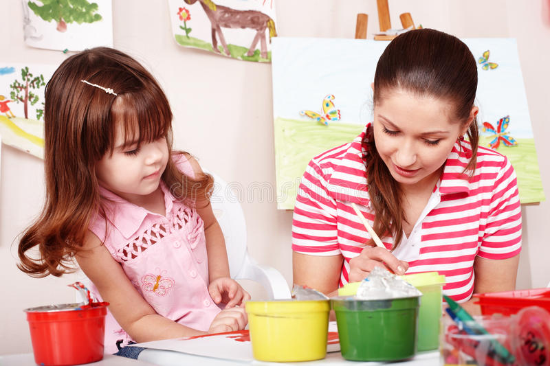 Child with teacher draw paints in play room. Preschool stock photo