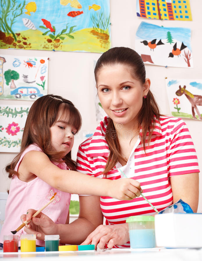 Child with teacher draw paints in play room. Preschool stock photos