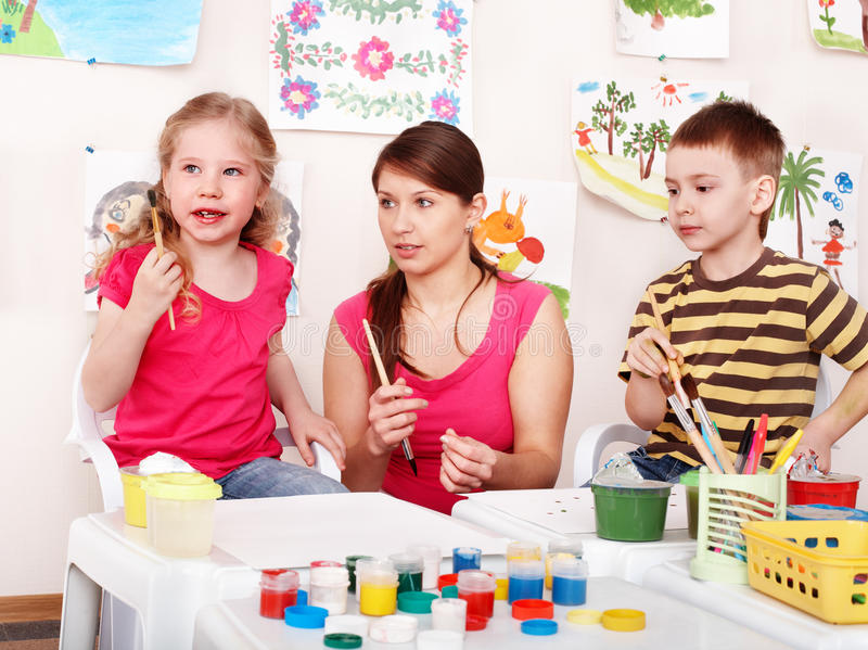 Child with teacher draw paints in play room. Preschool stock image
