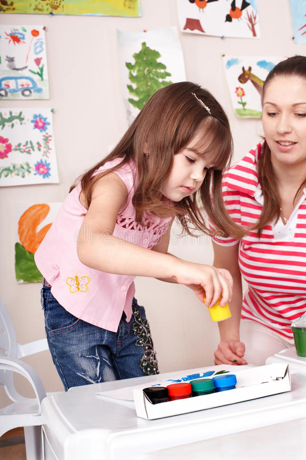 Child with teacher draw paints in play room. Preschool royalty free stock photo