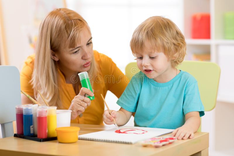 Child with teacher draw paints in play room. Preschool. stock photo