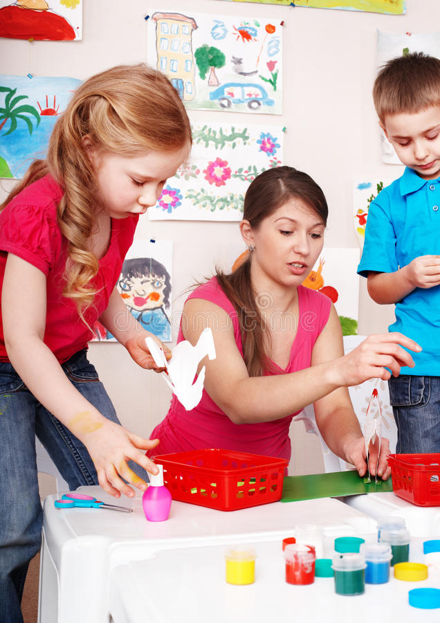Child with teacher in play room. stock photography