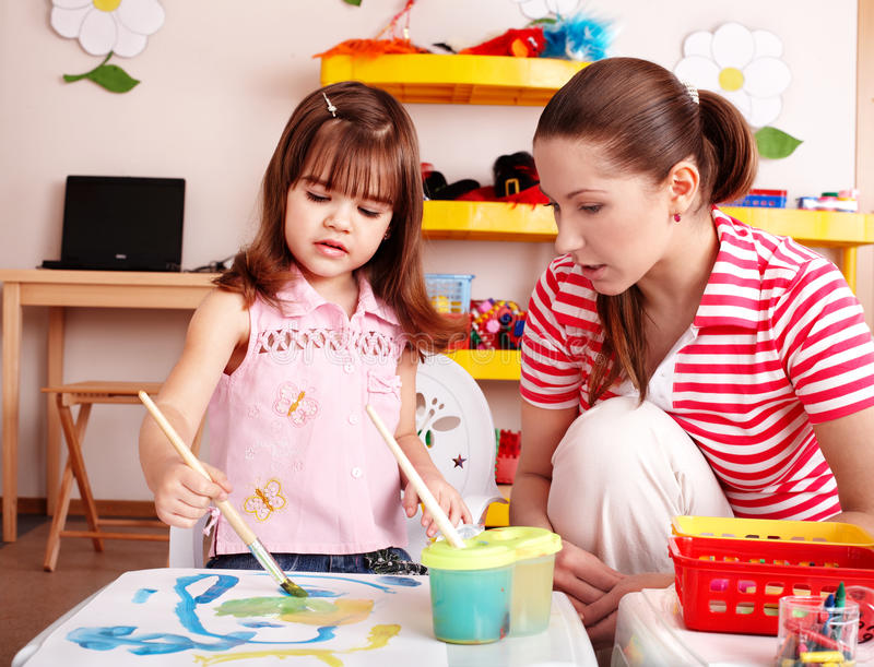 Child with teacher in play room draw paint . Child with teacher in play room draw paints . Preschooler stock images