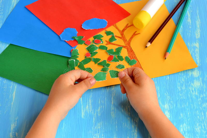 Child tearing colored paper into pieces. Home activity to improve fine motor skill development. Baby play. How to work with paper. Development of fine motor stock photography