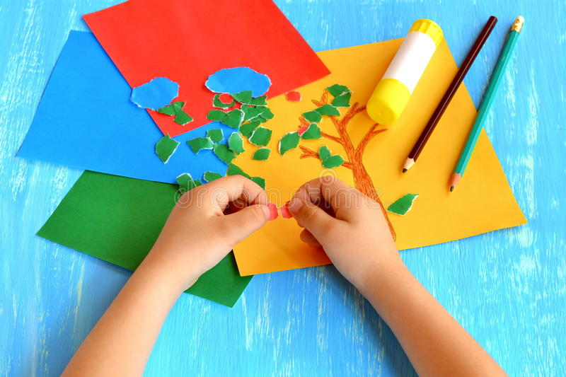 Child tears a red paper into small pieces. Child holds red paper pieces in his hands. Kindergarten art lesson royalty free stock image