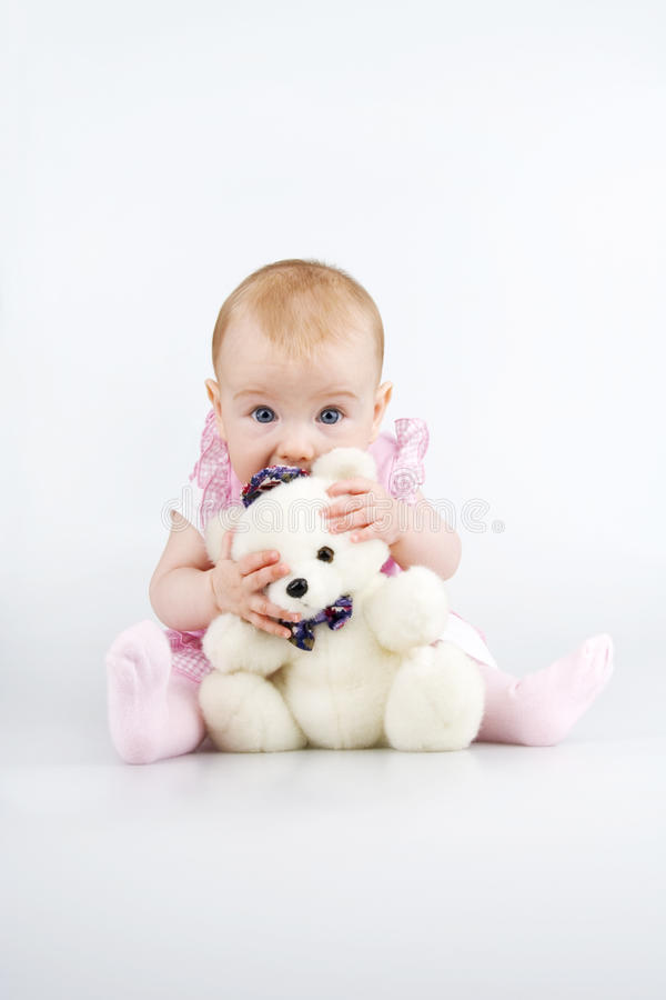 Child with teddy - bear. Beautiful little girl cowering behind plushy teddy - bear,on white background royalty free stock photo