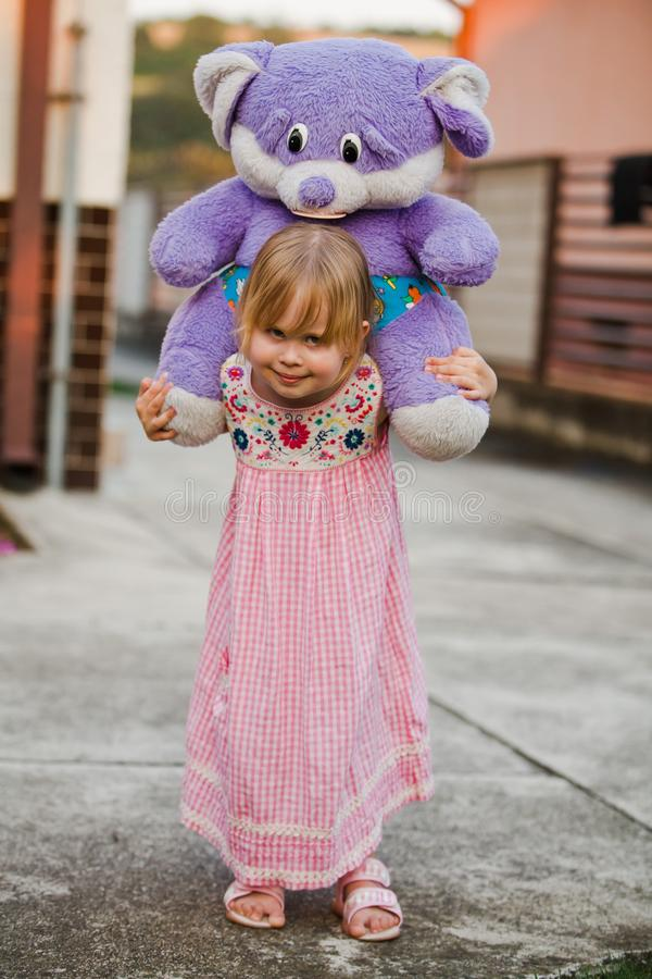 Child with big purple teddy bear. Child carry on her back big purple teddy bear. Holiday playing on the back yard stock images
