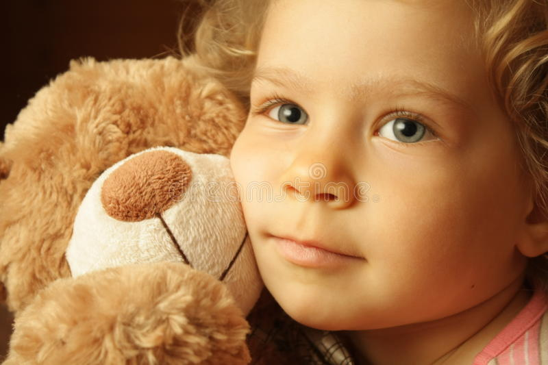 Child with a teddy bear stock images