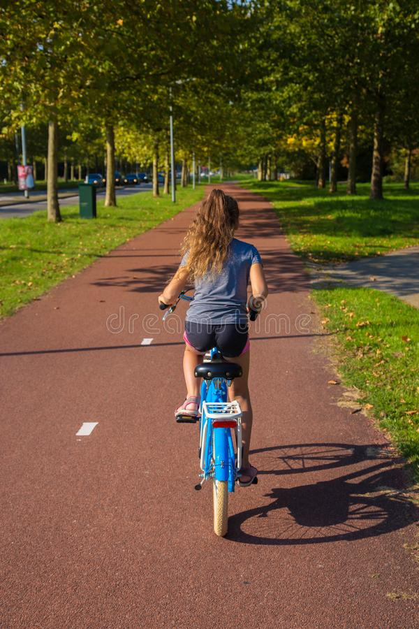 Child or teenager girl enjoys good weather and cycling stock photos