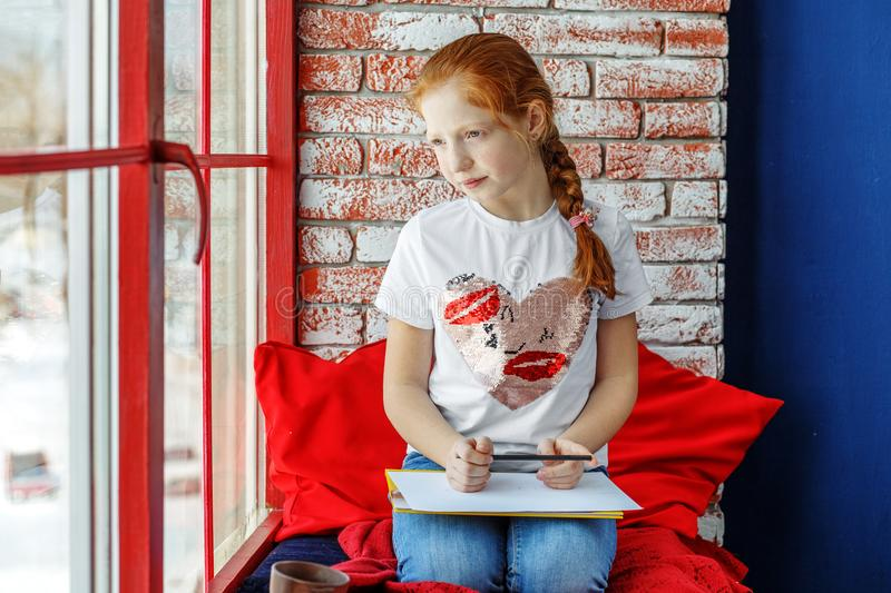 The child is a teenager sitting on the window sill and drawing. stock image