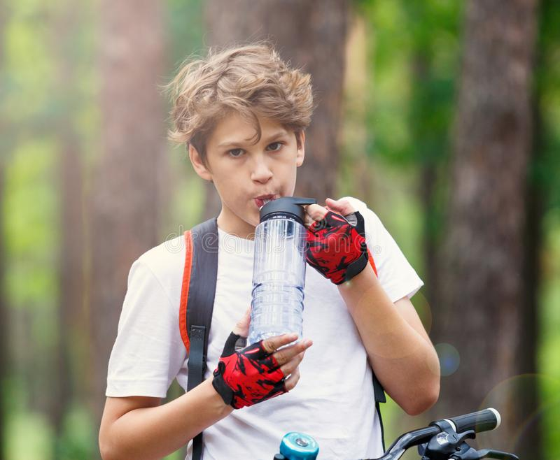 Child teenager in white t shirt and yellow shorts on bicycle ride in forest at spring or summer. Happy smiling Boy cycling outdoor stock images