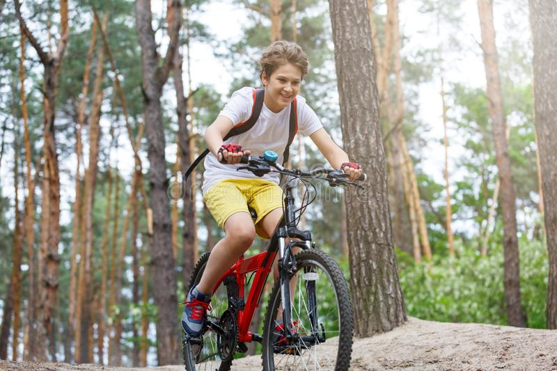 Child teenager in white t shirt and yellow shorts on bicycle ride in forest at spring or summer. Happy smiling Boy cycling outdoor. S Active lifestyle, hobby royalty free stock photography