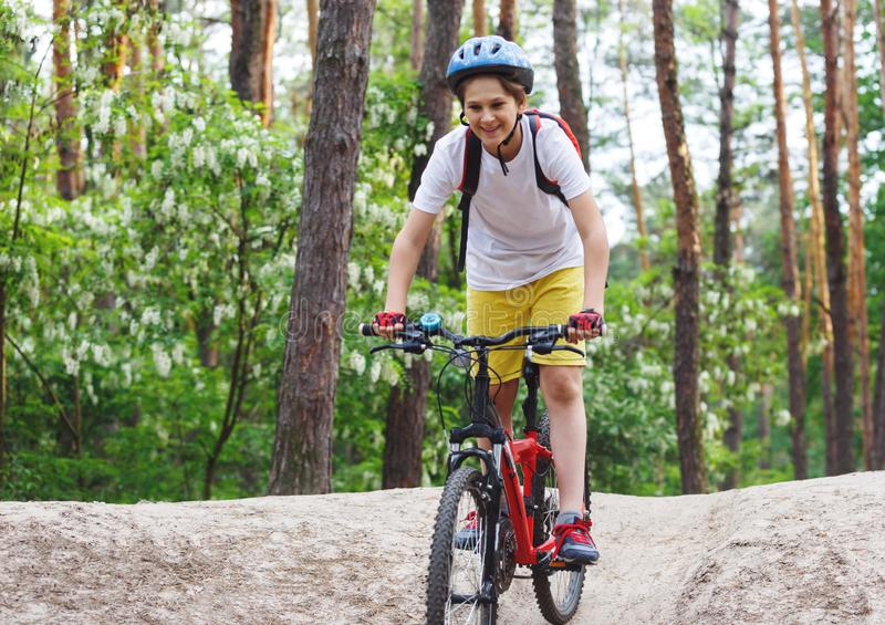 Child teenager in white t shirt and yellow shorts on bicycle ride in forest at spring or summer. Happy smiling Boy cycling. Outdoors in blue helmet. Active stock image