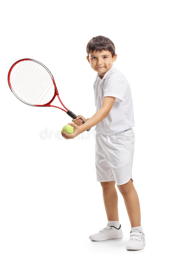 Child tennis player serving a ball with a racquet stock photography
