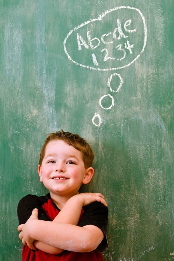 Child thinking about writing and math stock image